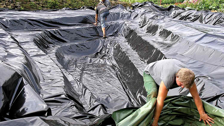 Die Baugrube des Teiches wird mit Schutzfolie ausgelegt, um sie vor Erosion zu schützen
