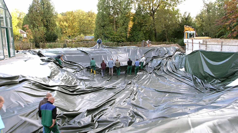 Fünf Personen ziehen eine große teichfolie in eine Teichgrube.