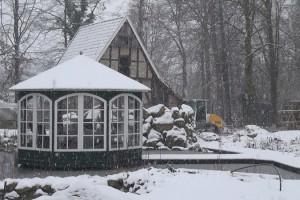 Ein Pavillon steht an einem vereisten Teich