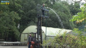 Mann steht erhöht auf einem Gabelstapler und lässt Wasser durch ein Rohr laufen