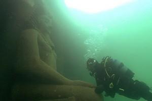 Taucher schwebt vor einer grossen Statue