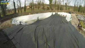 Mehrere Personen verlegen eine grosse Teiochfolie in eine Teichgrube