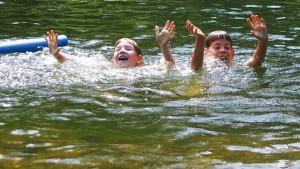 Kinder schwimmen in einem Teich
