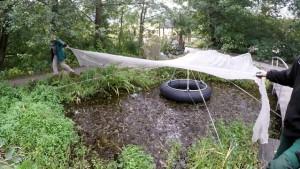 Zwei personen spannen ein Teichnetz über einen Gartenteich