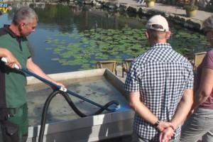 Messebesucher sehen eine Vorführung eines Schlammsaugers für Teiche