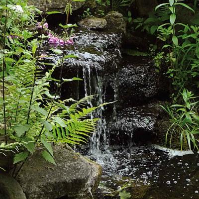 Ein kleiner Bachlauf plätschert aus einer naturnahen Steinformation; die Geräuschkulisse sollte vor dem Bau berücksichtigt werden.