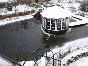 In Bereichen, wo sich das Wasser bewegt, bleibt die Oberfläche des Gartenteiches länger offen. Hier eine Felsenquelle hinter Pavillon.
