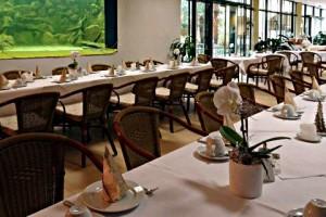 Der Gastraum des Palmen-Bistro mit eingedeckten Tischen.