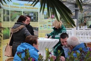Teichberater und Pflanzenspezialisten in der regengeschützten Palmenhalle.