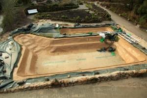 Ein fast fertiger Schwimmteich: Die Teichfolie ist nicht mehr sichtbar, der Boden hat eine natürliche Färbung.
