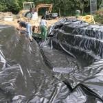 Regenjacke für den Teich: Die Sicherungsfolie wird über die Baugrube gelegt