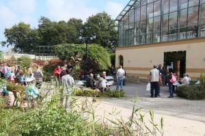 Besucher entspannen vor der Palmenhalle, Snacks bietet die Grillstation